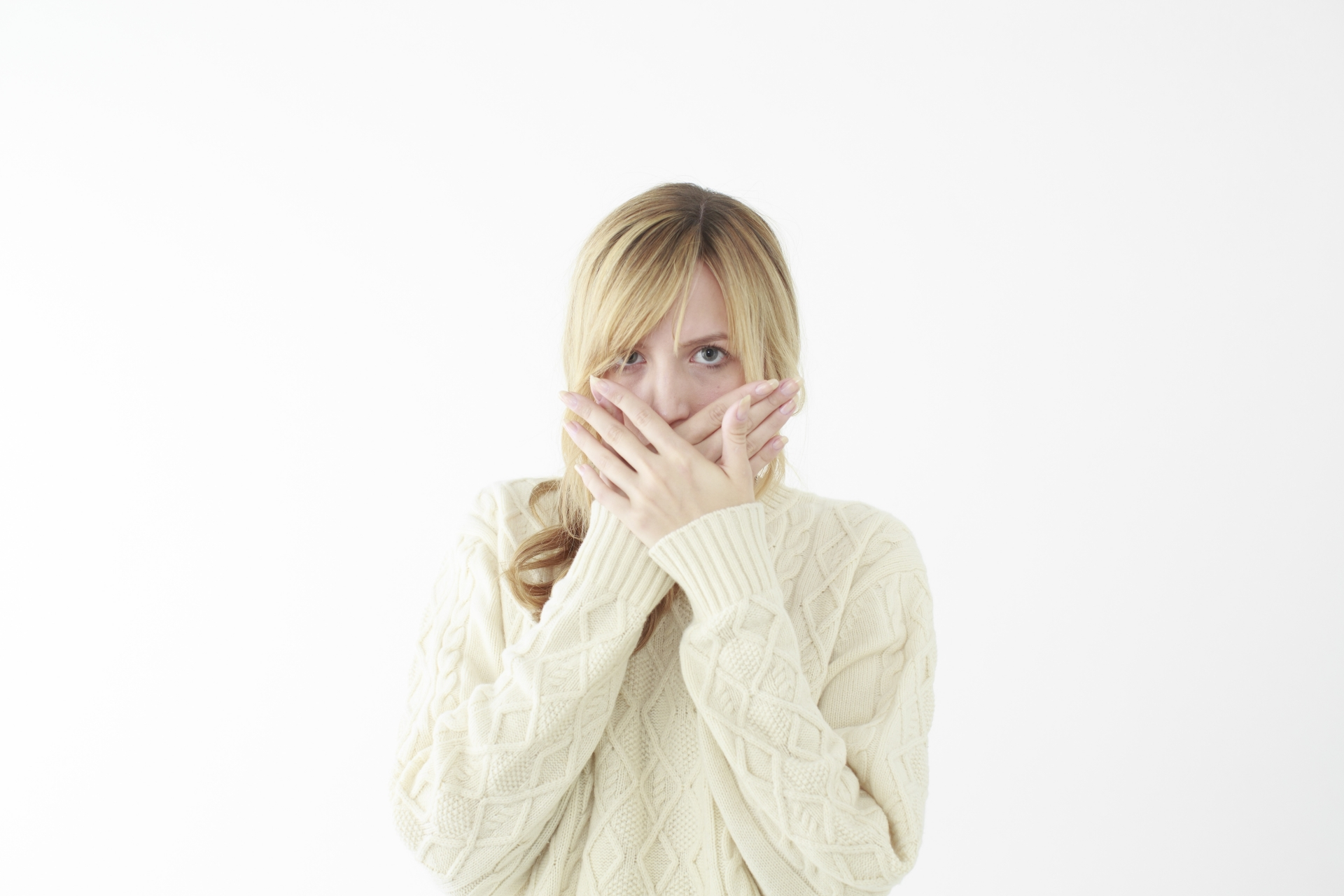前歯が取れて口を隠す女性