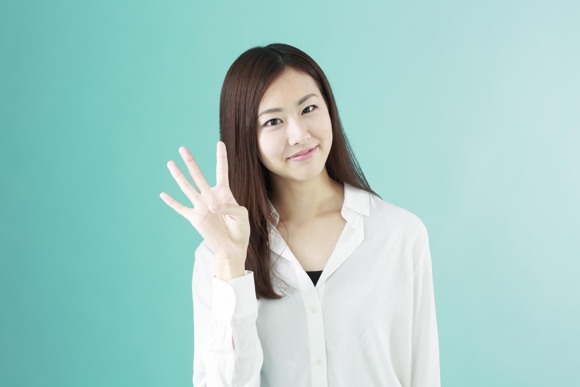 指で4を示す女性