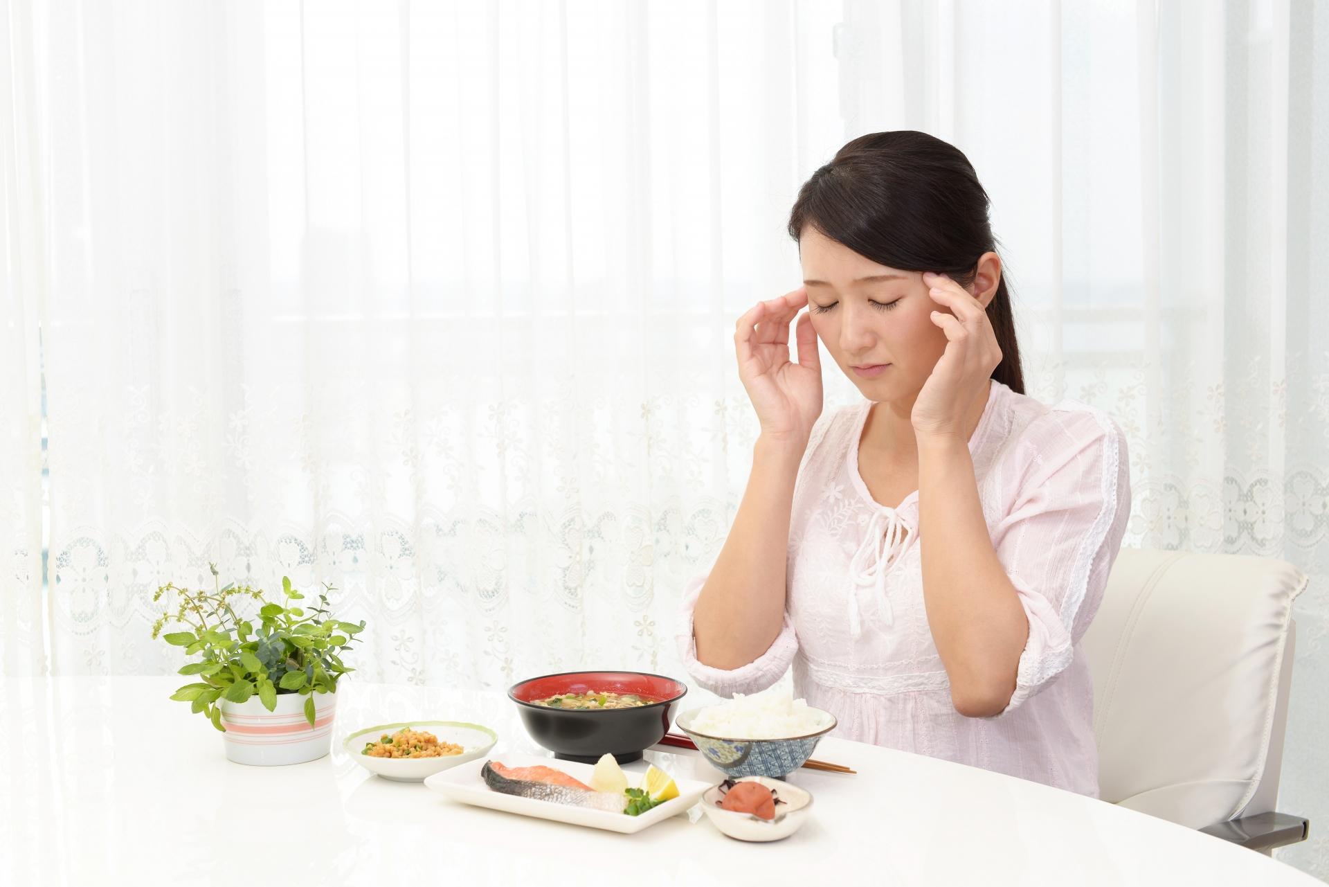 食事中に頭痛がして思わずこめかみを押さえる主婦